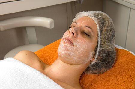 A woman is lying in a beauty salon with a facial mask on her face Stock Photo - 17497850