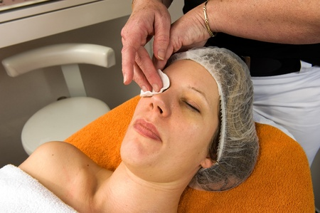 A woman s face is cleaned with a wad of cotton wool in a beauty salon Stock Photo - 17497841