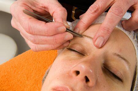 pinzas: Ceja mujer s se depilan en un salón de belleza