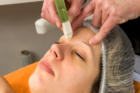 waxed: A woman s hair between her eyebrows is being waxed