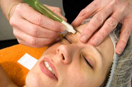 ヘット眉下の女性の毛のワックスします。 写真素材