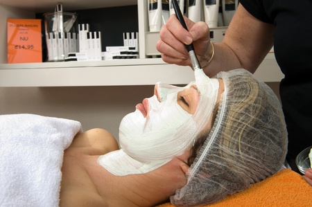 A woman is lying in a beauty salon and getting a facial mask on her face with a brush Stock Photo - 17497838