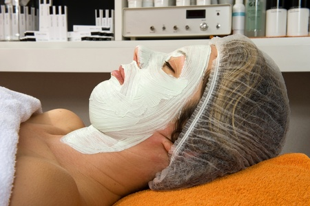 A woman is lying in a beauty salon with a facial mask on her face Stock Photo - 17497852