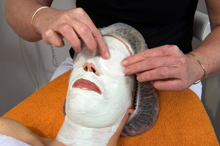 wads: A woman is lying in a beauty salon with a mask on het face while her eyes a covered with wads of cotton wool