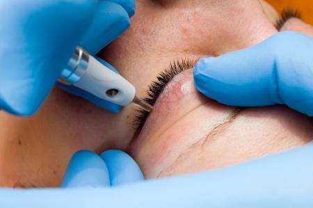 Eine Frau wird immer Permanent Make-up mit einer Nadel in einem Schönheitssalon