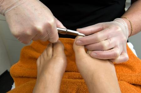 salon de belleza: Las u�as de una mujer s se cortan en sus dedos de los pies en un sal�n de belleza Foto de archivo