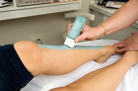 The leg of a woman is being depilated with wax in a beauty salon photo