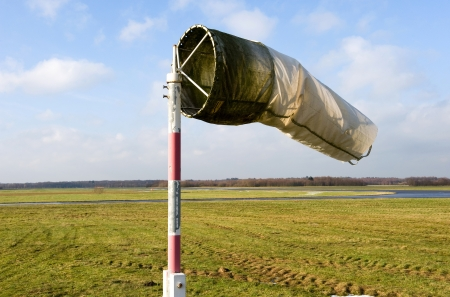A dirty old windsock on a closed airfield but still working photo