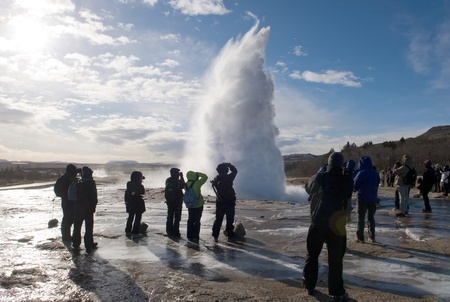 The Strokkur geyser in Iceland is erupting while tourists are looking photo