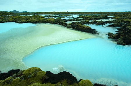 therapy geothermal: The blue water between the lava stones covered with moss just outside the Blue Lagoon resort of Iceland