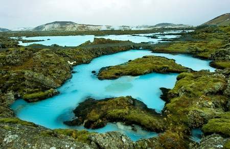 The blue water between the lava stones covered with moss just outside the Blue Lagoon resort of Iceland photo