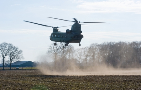 GEESTEREN, NETHERLANDS - MARCH 25: A Dutch Chinook helicopter is about to land on a field near a farm to pick up military soldiers during a practise, March 25, 2013.