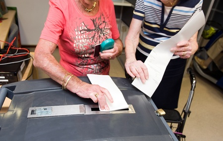 polling: Two woman with their ballots are gonna put them in a ballot box Stock Photo