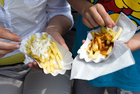 A mother and a child eating a box of french frites