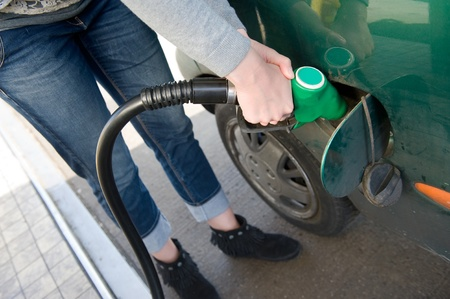 A woman is filling her car with fuel at a filling station photo