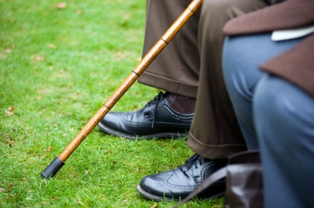 walking stick: An old man sitting with a walking stick in his hand