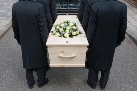 Bearers a carrying a coffin into a car Stock Photo