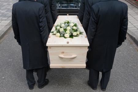 Bearers a carrying a coffin into a car Standard-Bild