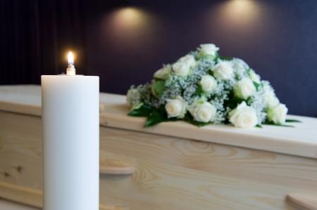 Een brandende kaars met een doodskist en een bloemstuk op de achtergrond in een mortuarium