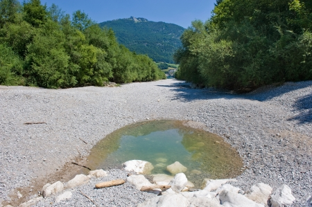 riverbed: A pond is al that is left in the dry riverbed of the Zinkenbach river in the summer who ends in the Wolfgangsee in Austria Stock Photo