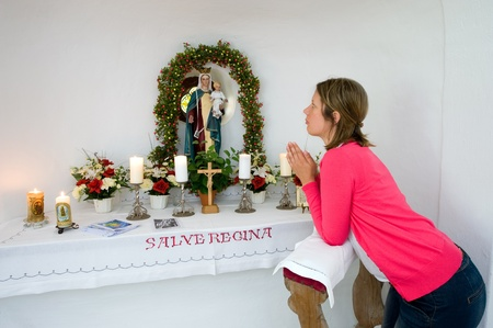 bible altar: A woman is praying in a small chapel Stock Photo