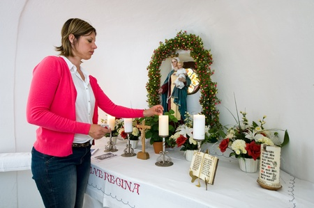 believing: A woman is lighting a candle in a small chapel