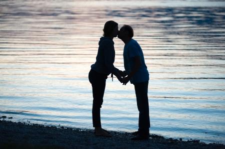 compromiso: Una pareja se besa en el crepúsculo en la playa de un lago Foto de archivo