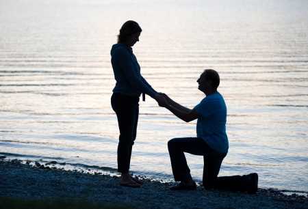 A man is doing a marriage proposal to his girlfriend photo