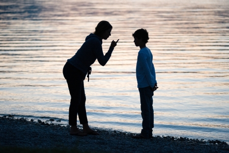 A mother is punishing her son in the evening on the beach of a lake photo