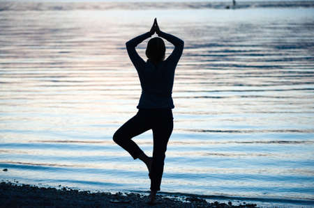 A woman is doing a workout on the beach of a lake in the evening photo