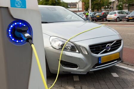 ENSCHEDE, The NETHERLANDS - SEPT 08  An electric car is parked at a parking spot in the centre of a town while he is being recharged at a power station, September 08, 2013 in the Netherlands