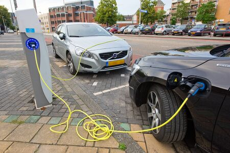 ENSCHEDE, The NETHERLANDS - SEPT 08  Two electric cars are parked at a parking spot in the centre of a town while they are being recharged at a power station, September 08, 2013 in the Netherlands