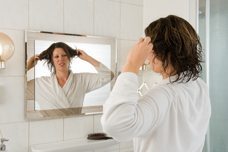 A woman is looking in the mirror of the bathroom and having a bad hair day. photo
