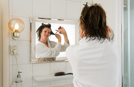 bad hair day: A woman is looking in the mirror of the bathroom and having a bad hair day, and wants to cut her hair