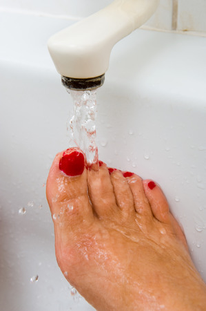 A woman is keeping her foot under the hot warm water of a bath faucet photo