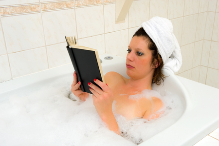 A woman is enjoying a hot bath with a towel around her hair and reading a book photo