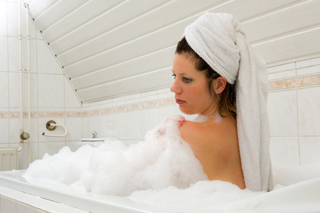 A woman is enjoying a hot bath with a towel around her hair Stock Photo - 22675805