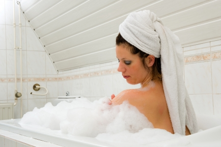 A woman is enjoying a hot bath with a towel around her hair Stock Photo - 22675807