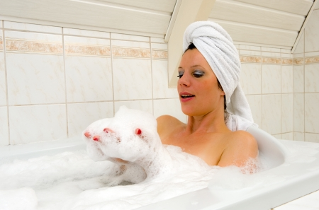 A woman is playing with foam and enjoying a hot bath with a towel around her hair  Stock Photo - 22675808