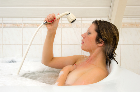 woman bathing: A woman is enjoying a hot bath and spraying water against her face