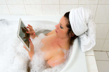A woman is playing with her while she is enjoying a hot bath photo