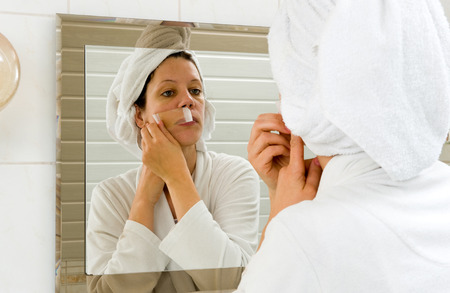 remover: A woman is depilating the small hairs from her moustache in front of a mirror