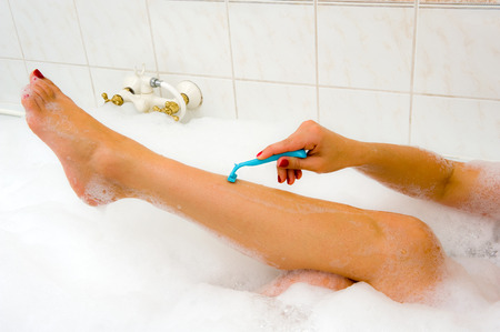 shaved: A woman is shaving her legs in the bathroom