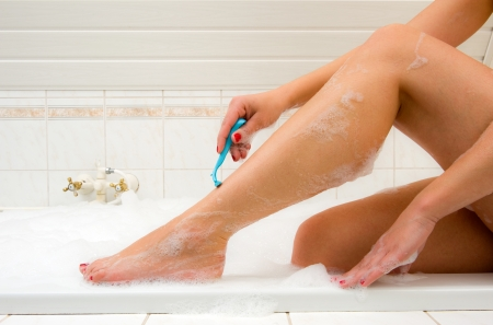 A woman is shaving her legs in the bathroom photo