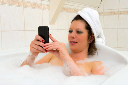 A woman is playing with her smartphone while she is enjoying a hot bath photo