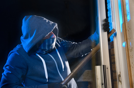 A burglar is opening the backdoor of a house photo