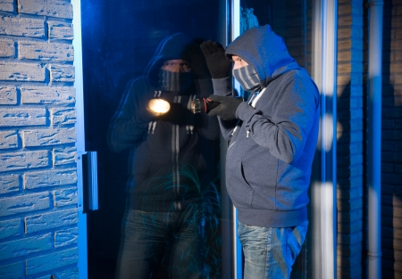 A burglar is looking through the window of a house