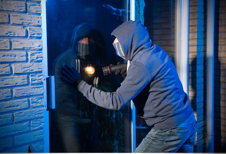 burglar protection: A burglar is looking through the window of a house