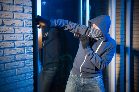 burglar protection: A burglar is opening the backdoor of a house