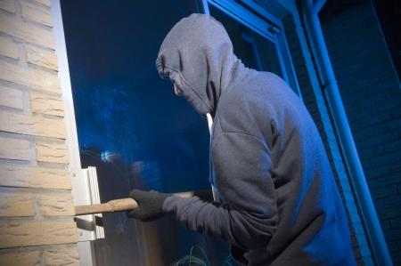 強盗は、バックドアによって、家に入るしようとしています。 写真素材